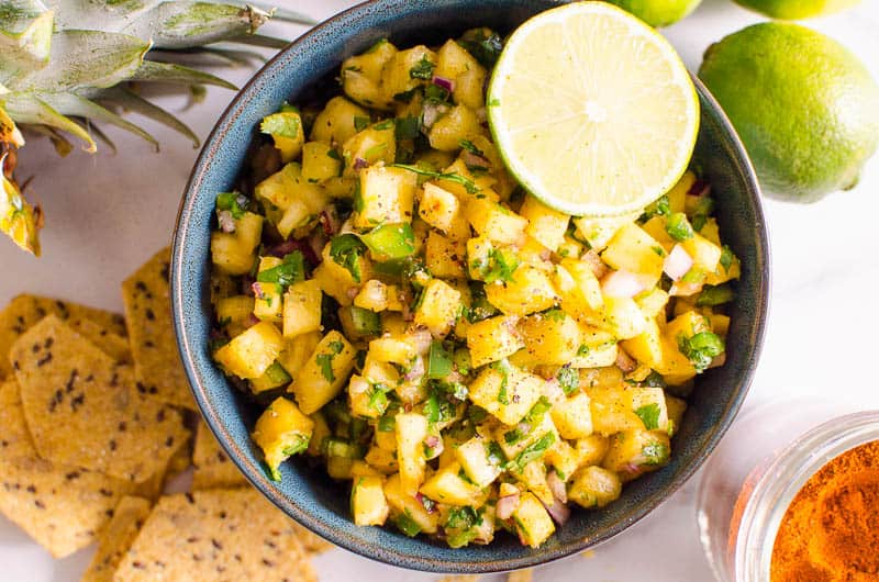 pineapple salsa recipe garnished with pepper and lime wedge