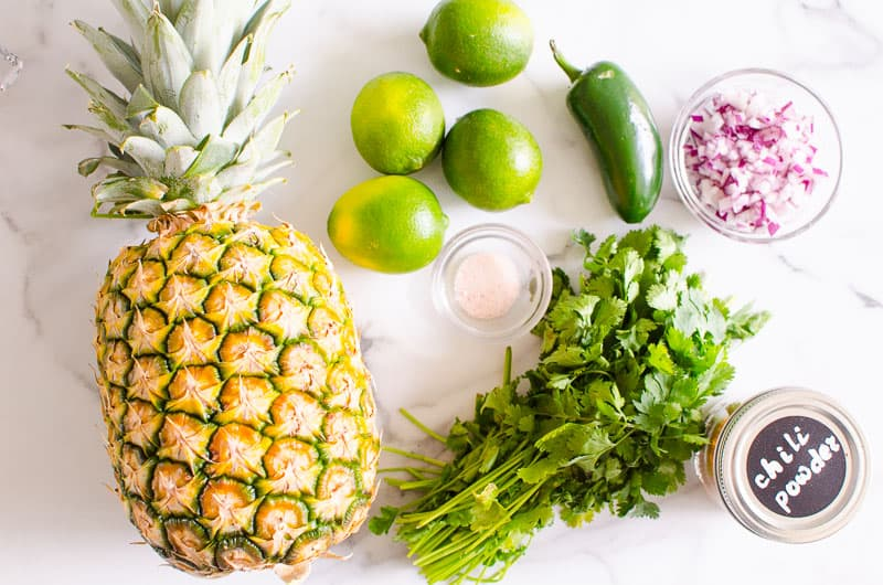 pineapple, limes, cilantro, red onion, jalapeno, spices on a countertop