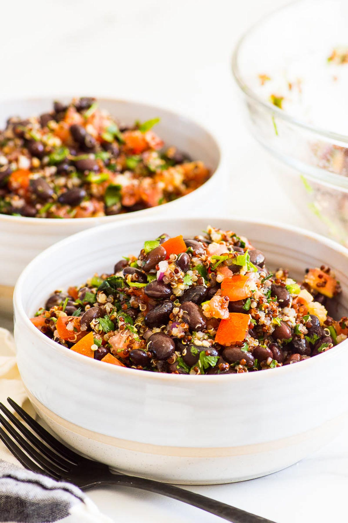 quinoa black bean salad in bowls with forks