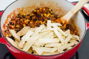 a pot with easy skillet enchiladas and corn tortillas on top