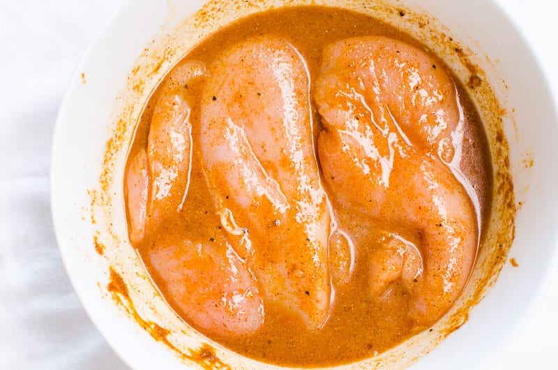 chili lime chicken marinade in a bowl with chicken breasts