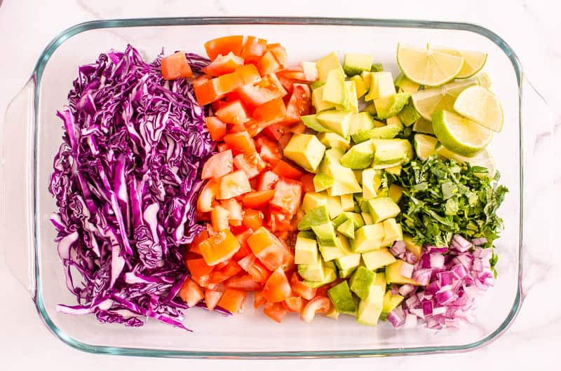 chopped red cabbage, avocado, tomato, cilantro and limes in a dish