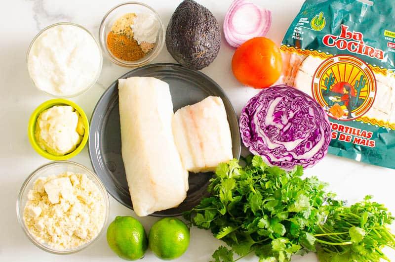 fish, corn tortillas, lime, cheese, avocado, tomato, cabbage, yogurt, spices, mayo, cilantro