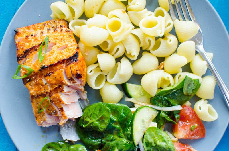 grilled salmon with pasta and salad on a plate