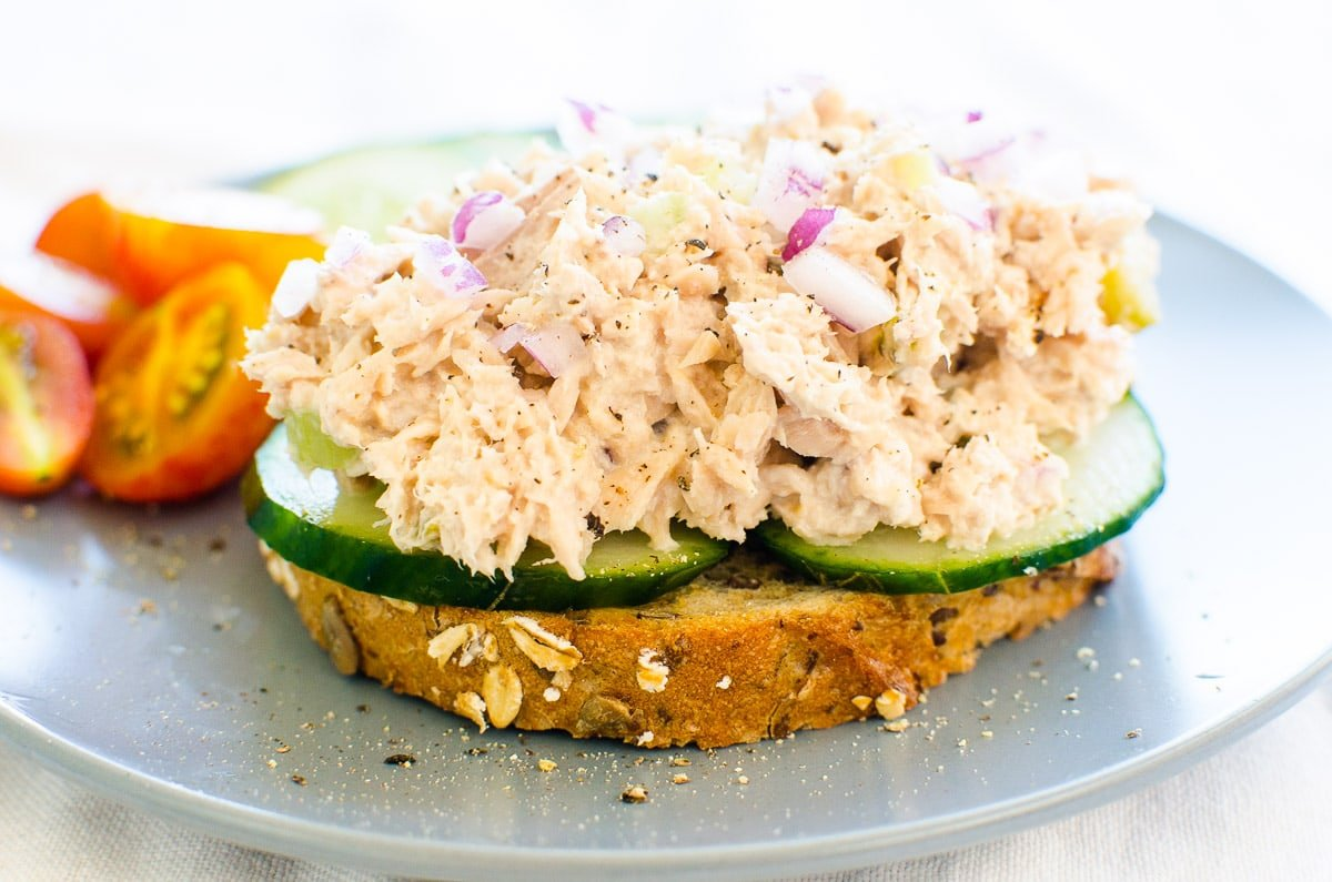 healthy tuna salad served on toast with cucumbers