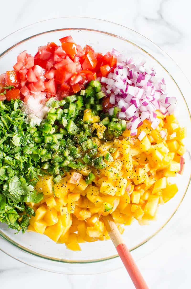 peach salsa ingredients in a bowl with a spoon