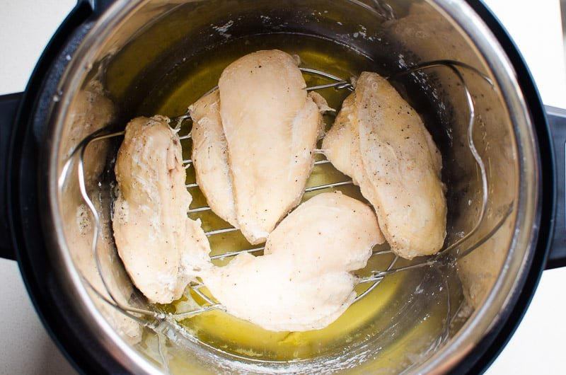 cooked frozen chicken breasts on a trivet in Instant Pot