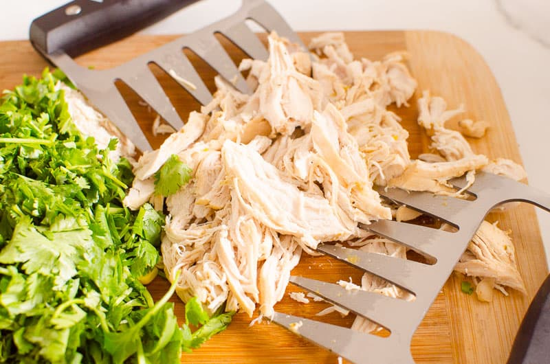 Instant Pot Shredded Chicken with meat claws on a board and cilantro nearby