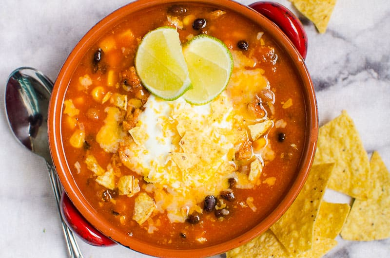 bowl of instant pot taco soup garnished with cheese, tortilla chips and lime