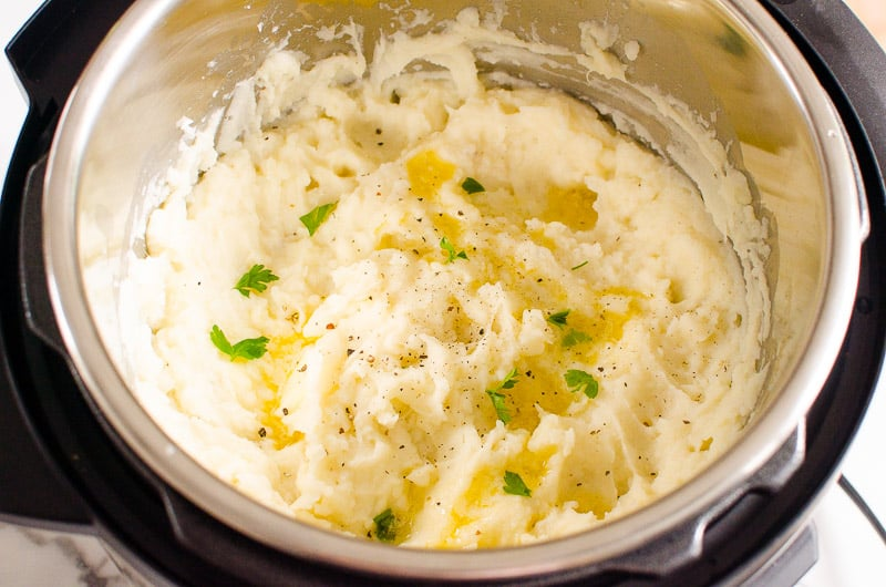 instant pot mashed potatoes recipe garnished with parsley and pepper
