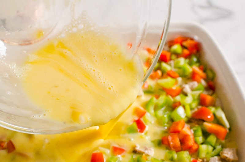 pouring egg mixture for breakfast casserole
