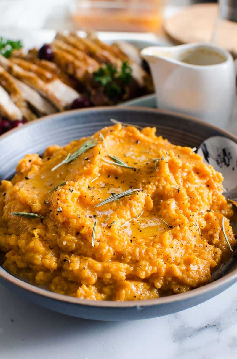 Mashed Sweet Potatoes in a blue bowl with a spoon garnished with rosemary