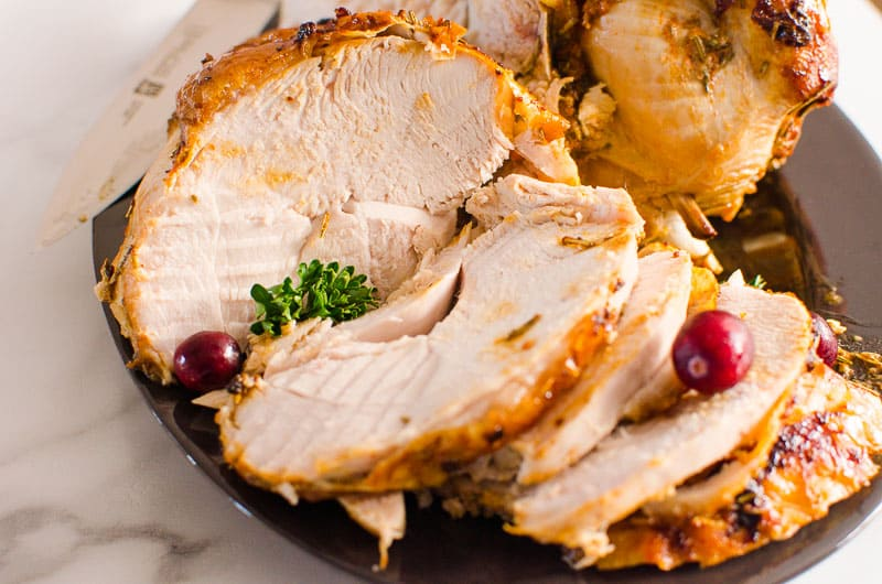 sliced roast turkey breast on a plate garnished with cranberries