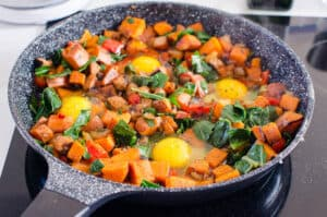Sweet Potato Hash and eggs in a skillet
