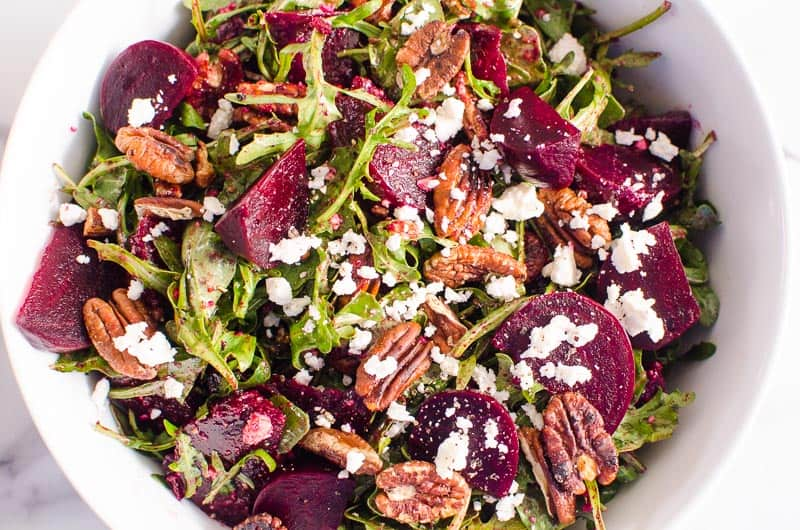 Beet salad with arugula, feta and pecans in a large white salad bowl