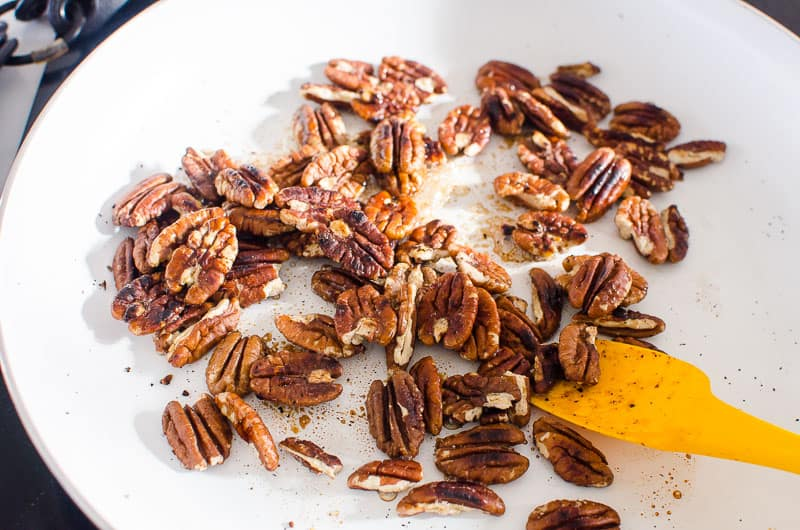 pecans in white skillet with yellow spatula
