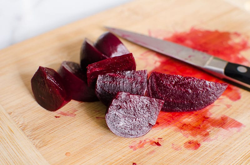 sliced beets on a cutting board with a knife