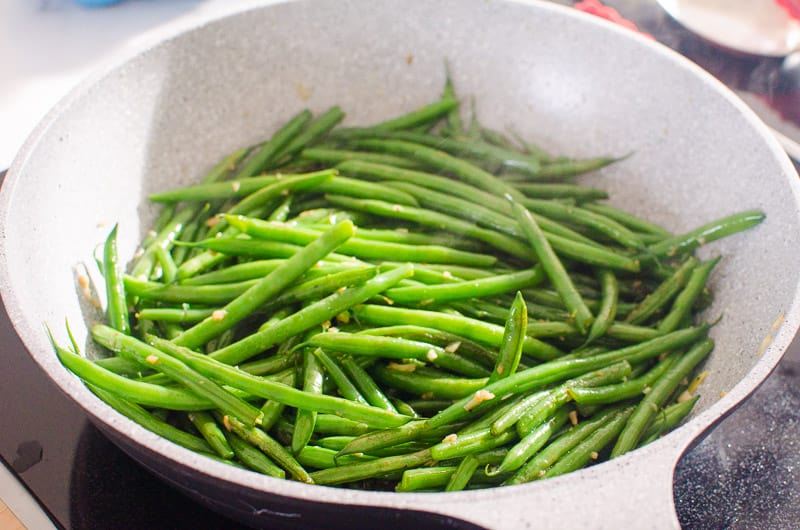 sauteed green beans with garlic in a grey skillet