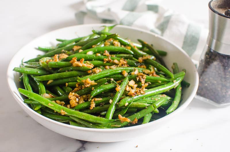 Garlic Green Beans in a white bowl with towel and pepper jar on a table