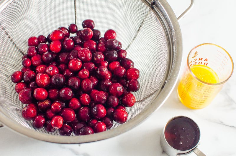 fresh cranberries in a colander, orange juice and maple syrup