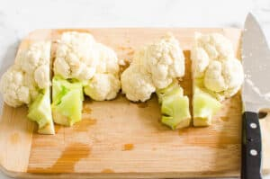 sliced cauliflower head into 4 quarters on a cutting board