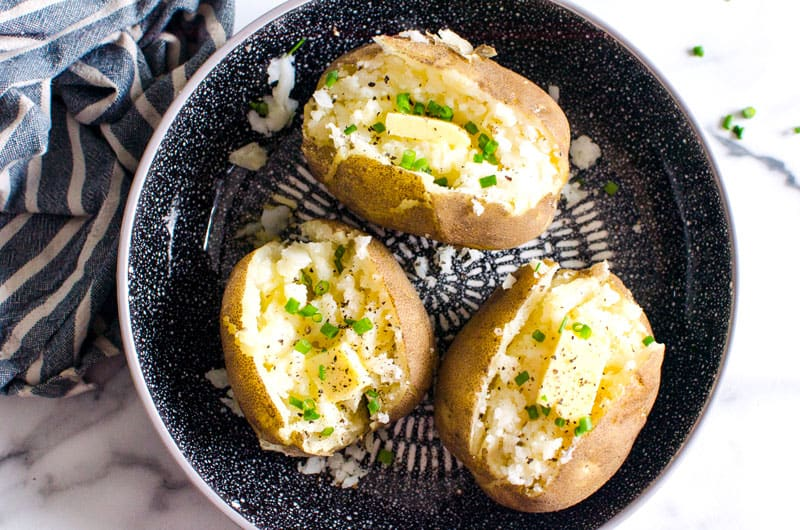 Instant Pot Baked Potatoes on a plate garnished with butter and chives