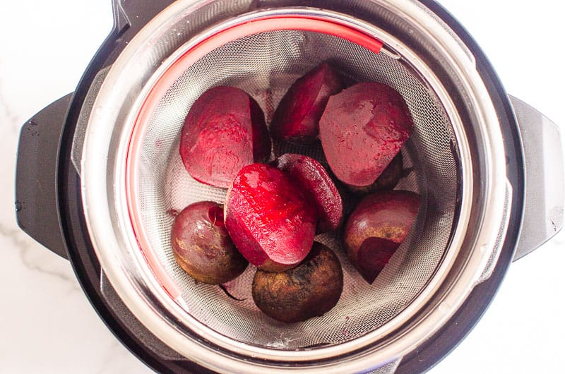 sliced raw beets in a steamer basket inside instant pot