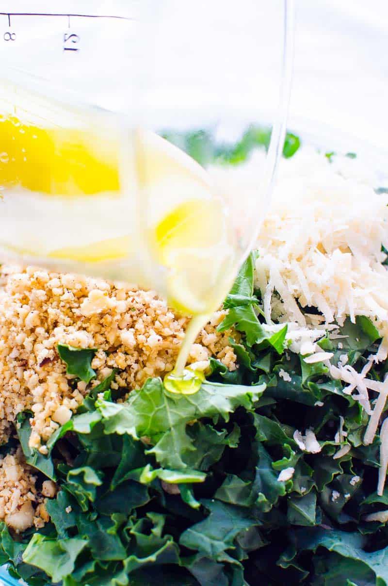 lemon dressing pouring over kale salad