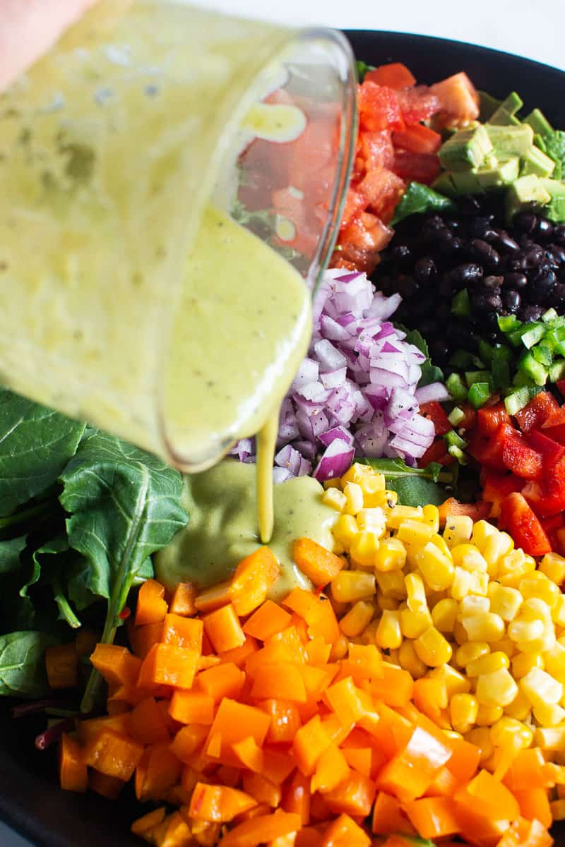 pouring avocado dressing over mexican kale salad ingredients