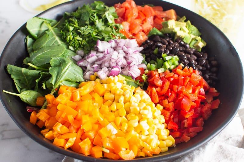corn, black beans, avocado, tomato, red onion, pepper in black bowl