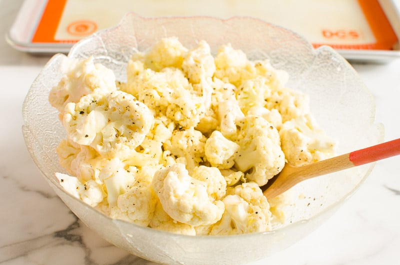 cauliflower florets seasoned with oil, salt and pepper in a glass bowl and stirred with wooden spoon