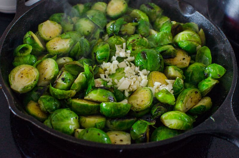 brussels sprouts and garlic in a cast iron skillet