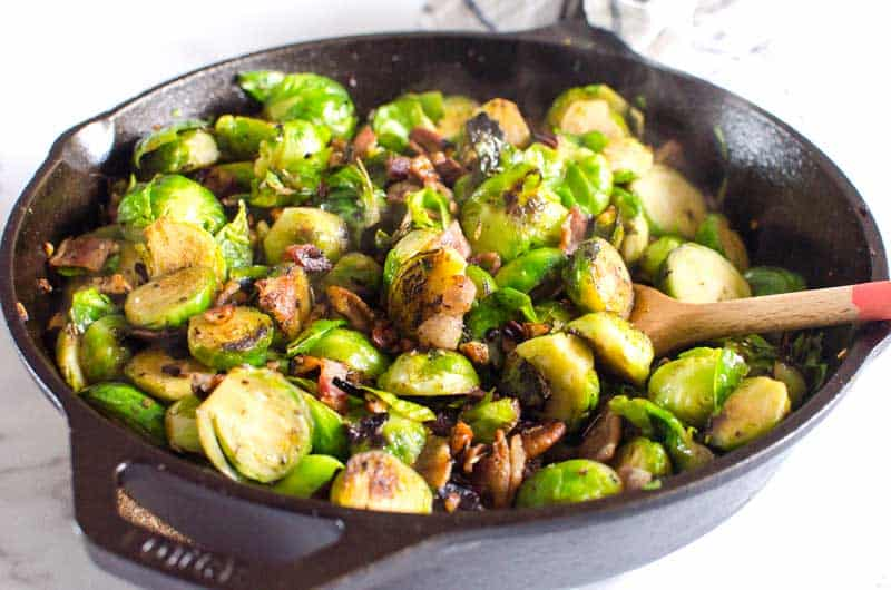 Sauteed Brussels Sprouts in a cast iron skillet with a wooden spoon