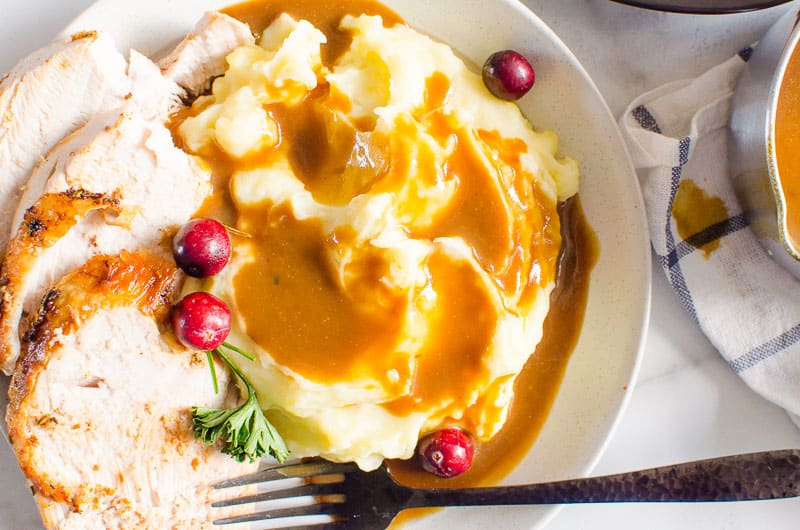 mashed potatoes with gravy, sliced turkey breast garnished with cranberries and black fork on a plate