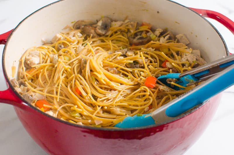 One Pot Turkey Tetrazzini in red pot with blue tongs
