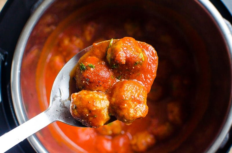 4 instant pot meatballs in tomato sauce on a spoon