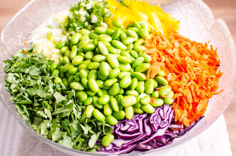 edamame, purple cabbage, carrots, cilantro, bell pepper and lettuce in a glass salad bowl