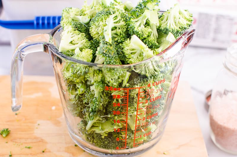 glass measuring cup full of broccoli florets