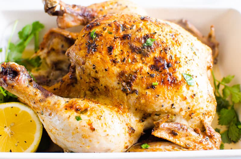 Instant Pot Whole Chicken on a platter with lemon and parsley