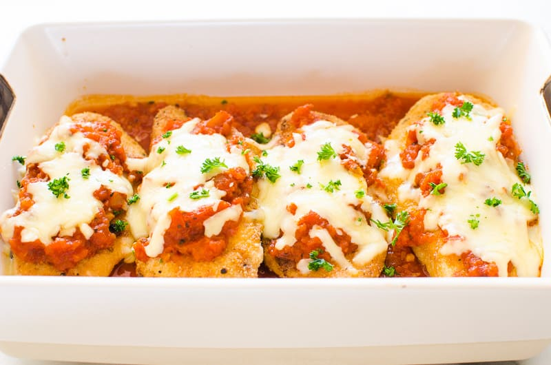 Healthy Chicken Parmesan garnished with parsley in white baking dish
