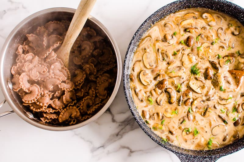 bowl of cooked pasta with wooden spoon and mushroom stroganoff