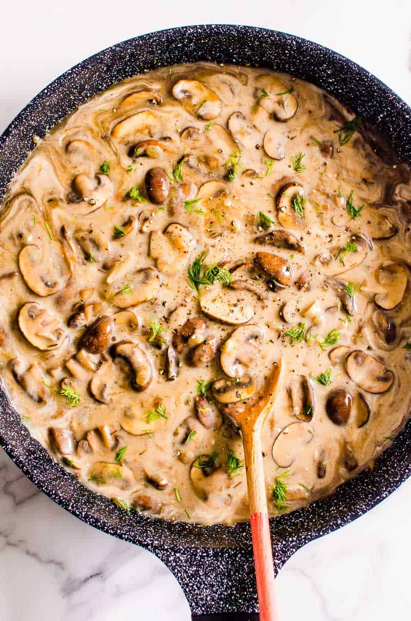 skillet of mushroom stroganoff with wooden spoon garnished with dill