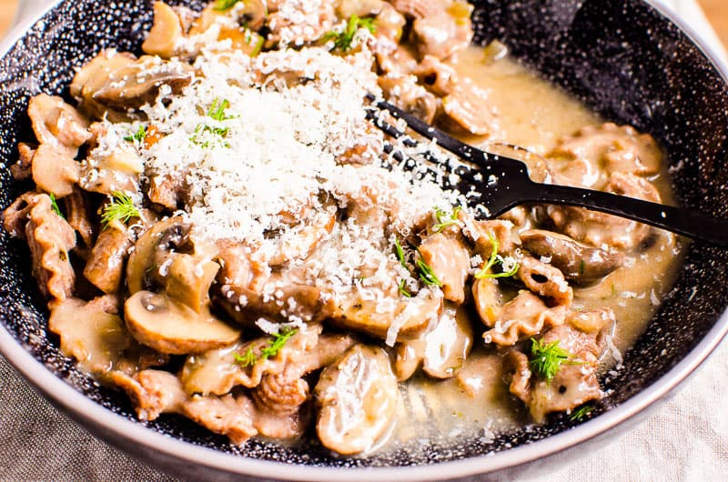 bowl of mushroom stroganoff with fork garnished with parmesan and dill