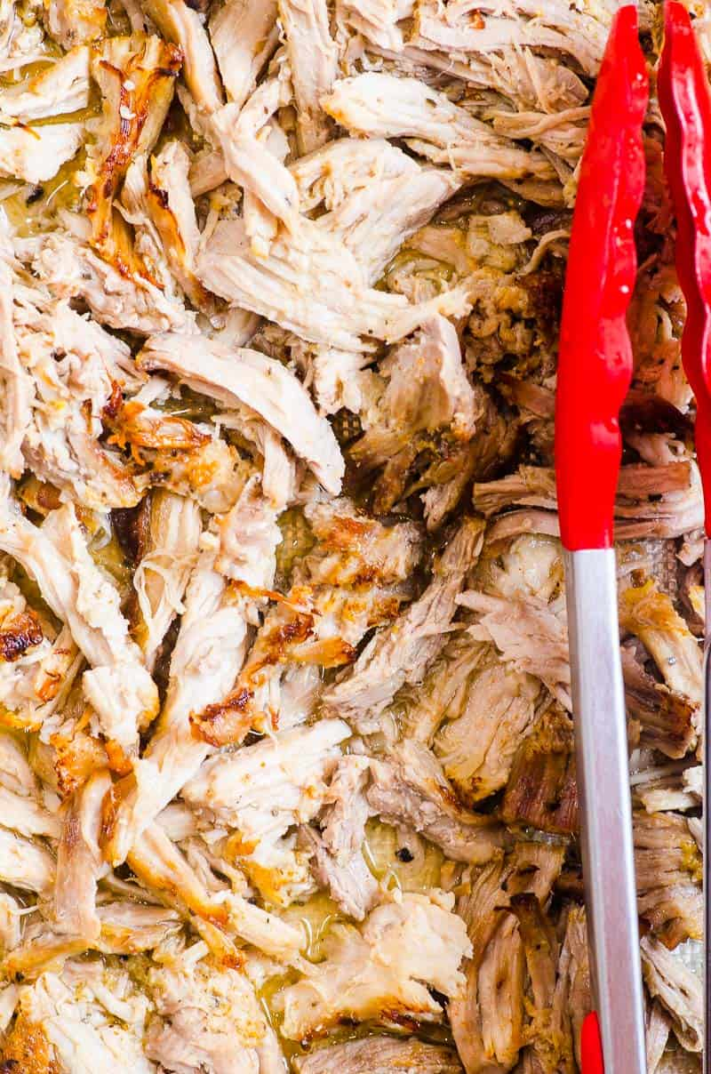 shredded Instant Pot pork carnitas with red tongs on a tray
