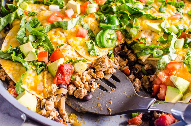 Taco Skillet scooped up with spatula and garnished with traditional taco fixings