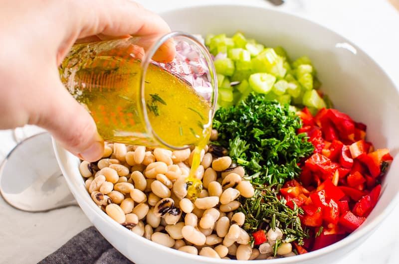 pouring dressing over White Bean Salad ingredients in a bowl