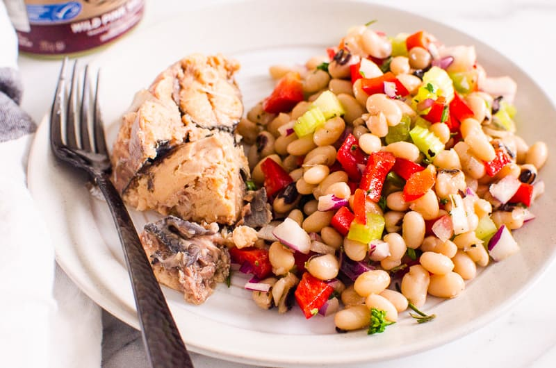 cannellini bean salad served with canned salmon on white plate