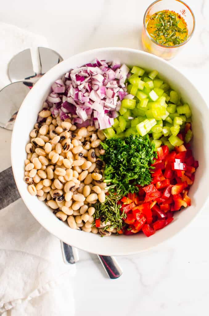 navy white beans, red onion, celery, red bell pepper, parsley in white bowl