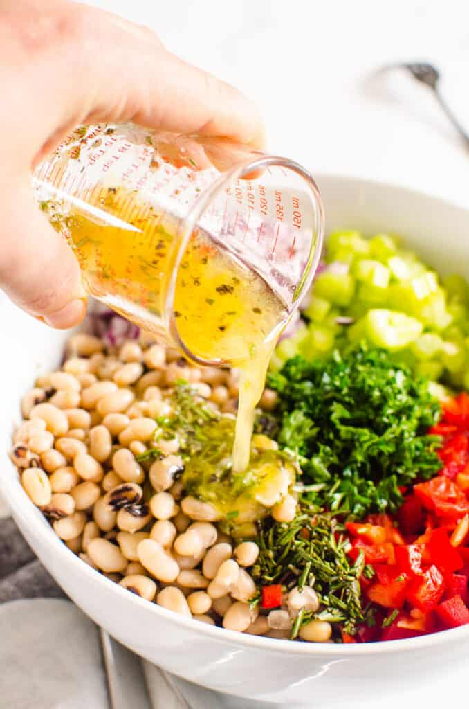 pouring dressing over white bean salad ingredients in white bowl