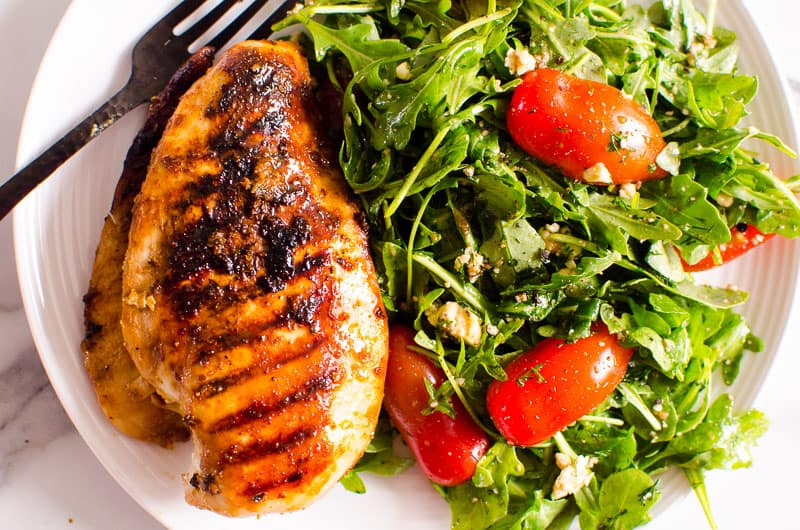 Arugula Salad with fajita chicken on white plate